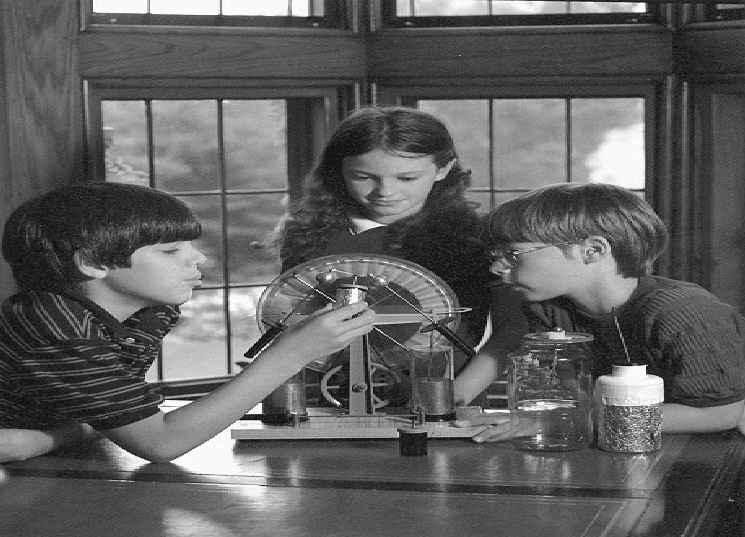 The Bakken 265 Fig. 8. The children are examining a Wimshurst static-electricity generator and some chargestorage devices, one of them a facsimile Leyden jar using foil to collect charge.