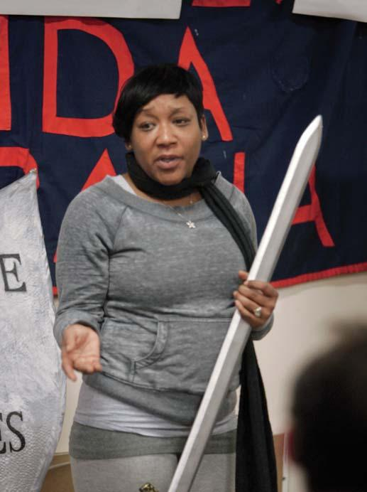 , City Life/ Vida Urbana organizer Melonie Griffiths explains the symbolic sword and shield used by City Life to represent its dual strategy (public pressure combined with zealous advocacy) in