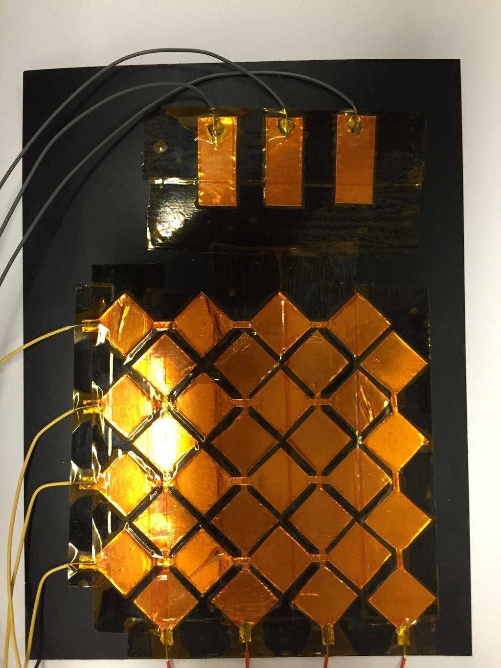 template. To isolate the capacitive plate from the user, the grid and pads were covered in Kapton Tape, a thin, transparent, and electrically insulating material.