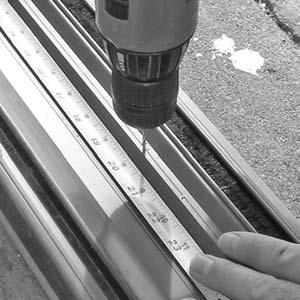 "Drill a second 3/32"" pilot hole at 20"" out from the side jamb (FIGURE 2). 3. Repeat Steps 1 and 2 for the opposite side of the sill track. 4."