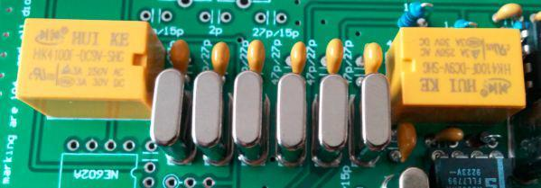 You don't need to place insulators under the crystals or ground the crystal cases Solder 7 each 47 pf capacitors Solder 2 each relays. When finished, it will look like the photo below Plug in a 12~13.