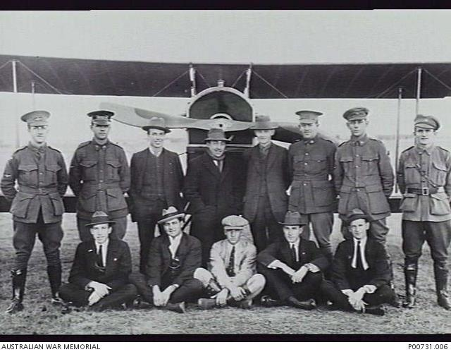 Photo 1917 - Group portrait of members of the third course of trainee pilots at the NSW State Aviation School in front of a Curtiss Jenny (JN) aircraft at Ham Common near Richmond.